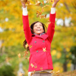 Happy fall xwoman throwing autumn leaves up in the air smiling blissful and cheerful in autumn forest. Young beautiful multicultural Caucasian / Asian xwoman model outside.